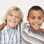 Portrait of a two cute little male friends smiling together on white